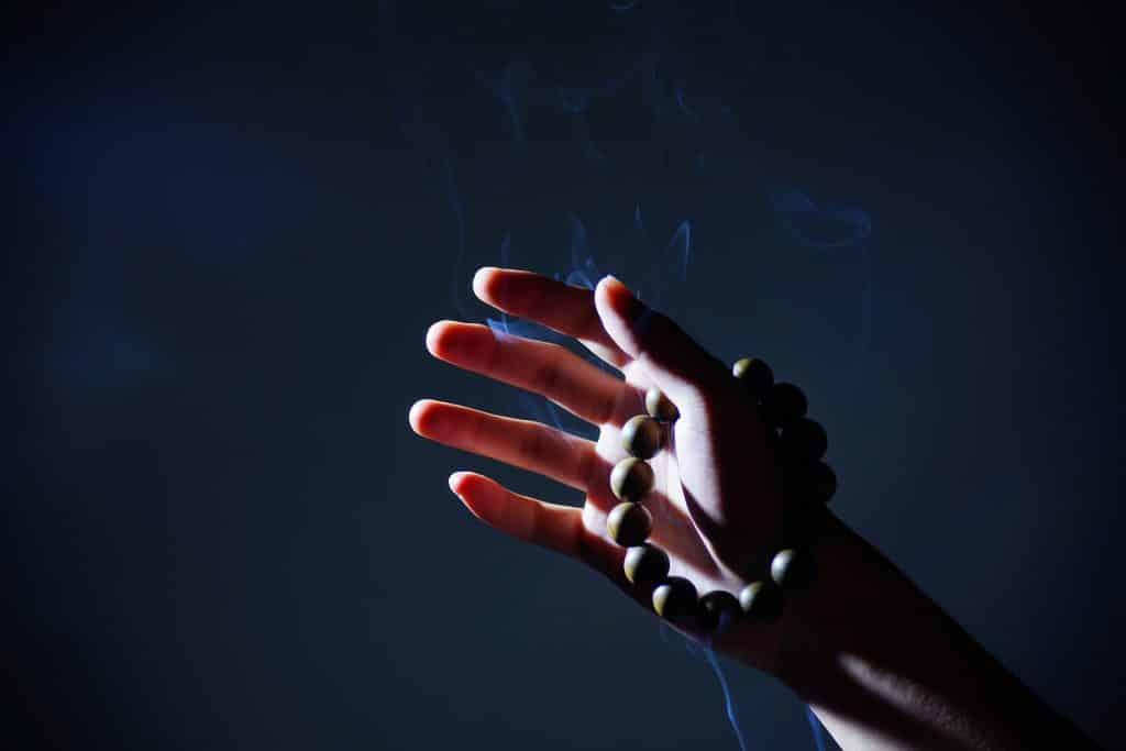 Imagem de uma mão levantada e nela uma pulseira de contas. A pessoa está querendo fazer a oração do perdão.