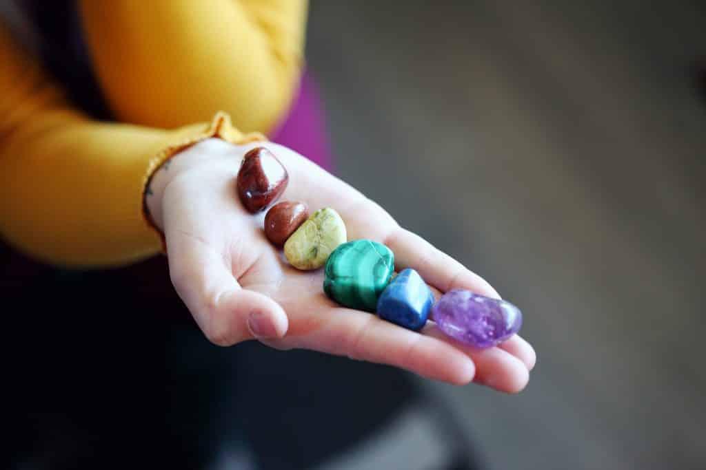 Imagem da mão de uma mulher e na palma da mão 07 pedras coloridas representando cada uma delas os nossos chakras.