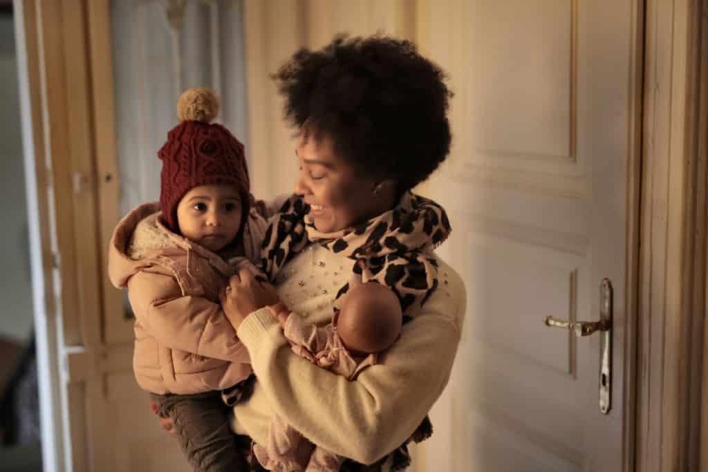 Mãe segurando sua filha bebê e uma boneca de brinquedo no colo.