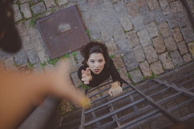 Mulher em escada vista de cima pedindo ajuda com mão para cima e mão oferecendo ajuda