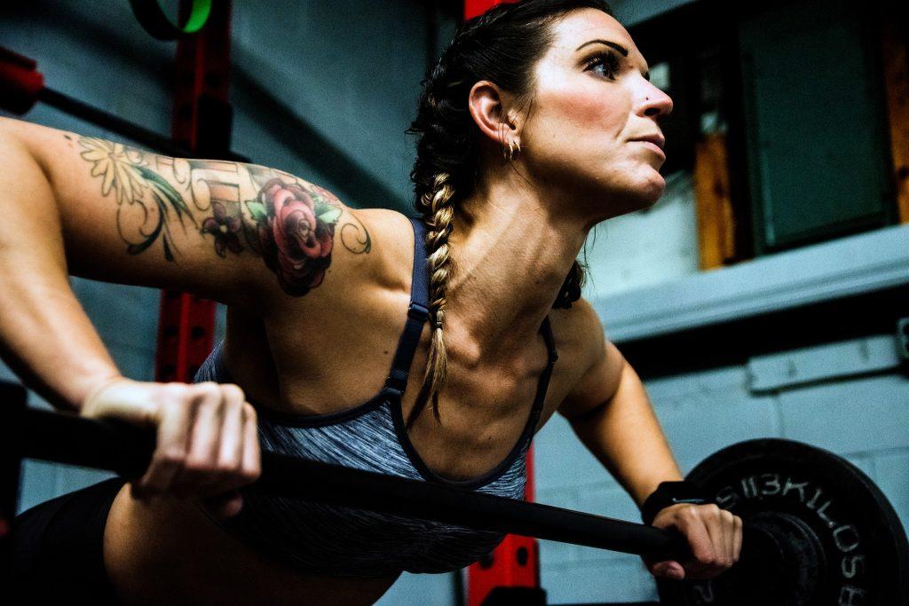 Imagem de uma mulher praticando atividade física em uma academia, Ela está levantando peso.