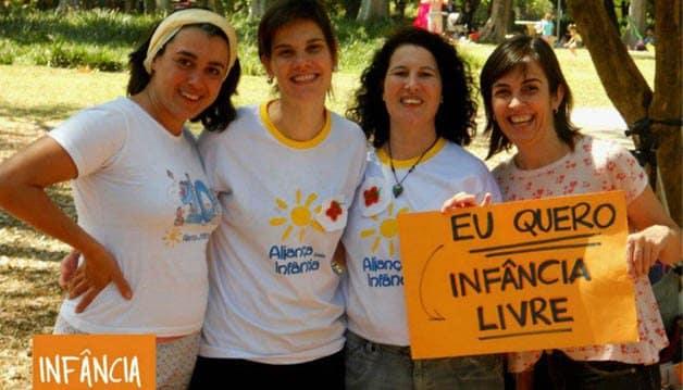 """Foto de quatro mulheres segurando um cartaz laranja escrito """"eu quero infância livre""""."""