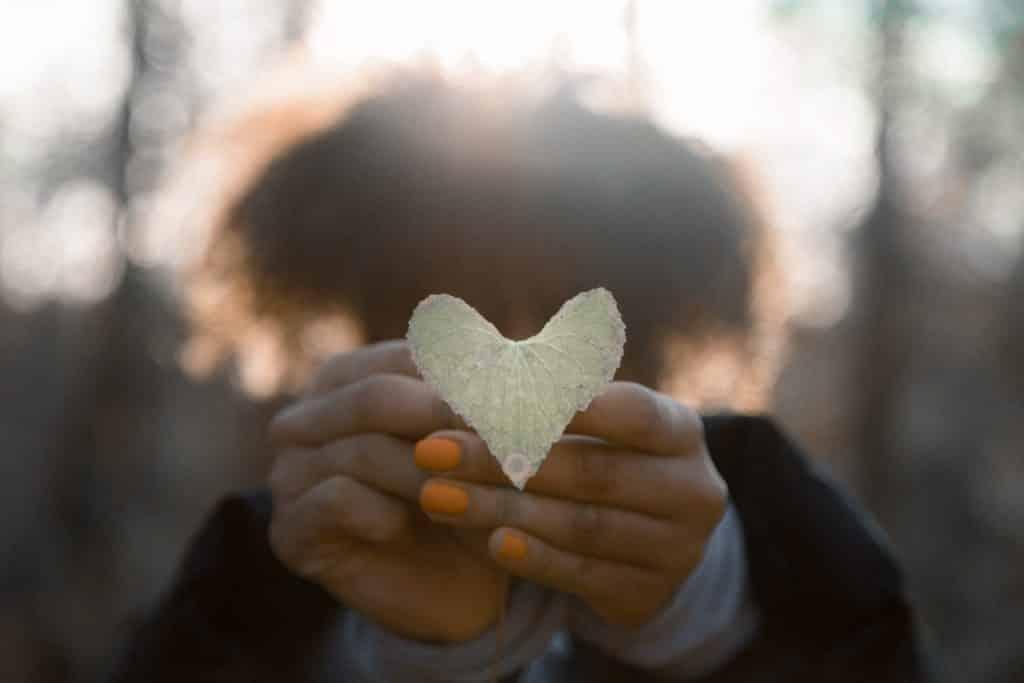Mulher segurando uma folha em forma de coração