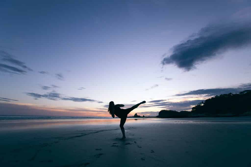 Mulher praticando artes marciais na praia