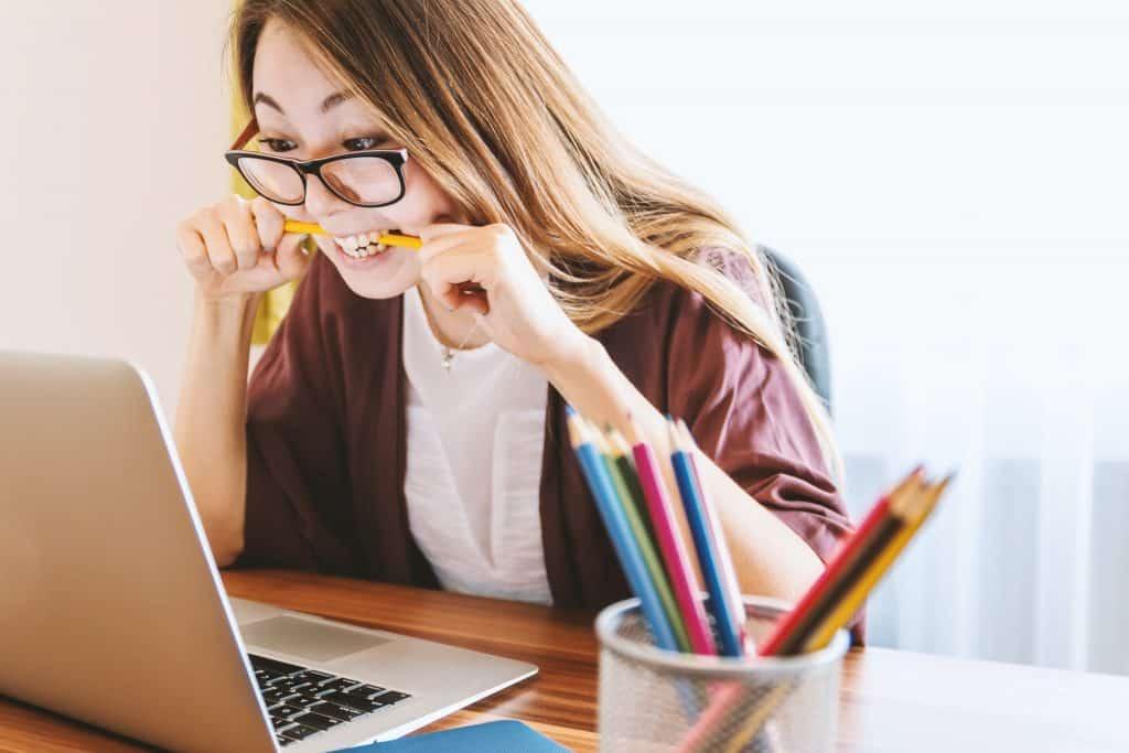 Mulher mordendo um lápis em frente a um computador, em sinal de estresse.
