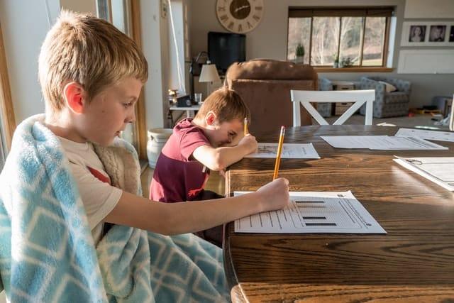 Irmãos fazendo lição de casa na mesa