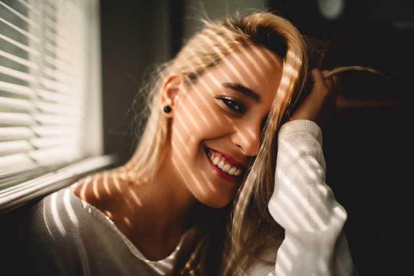 Mulher sorrindo ao lado de uma janela apoiando seu braço na cabeça