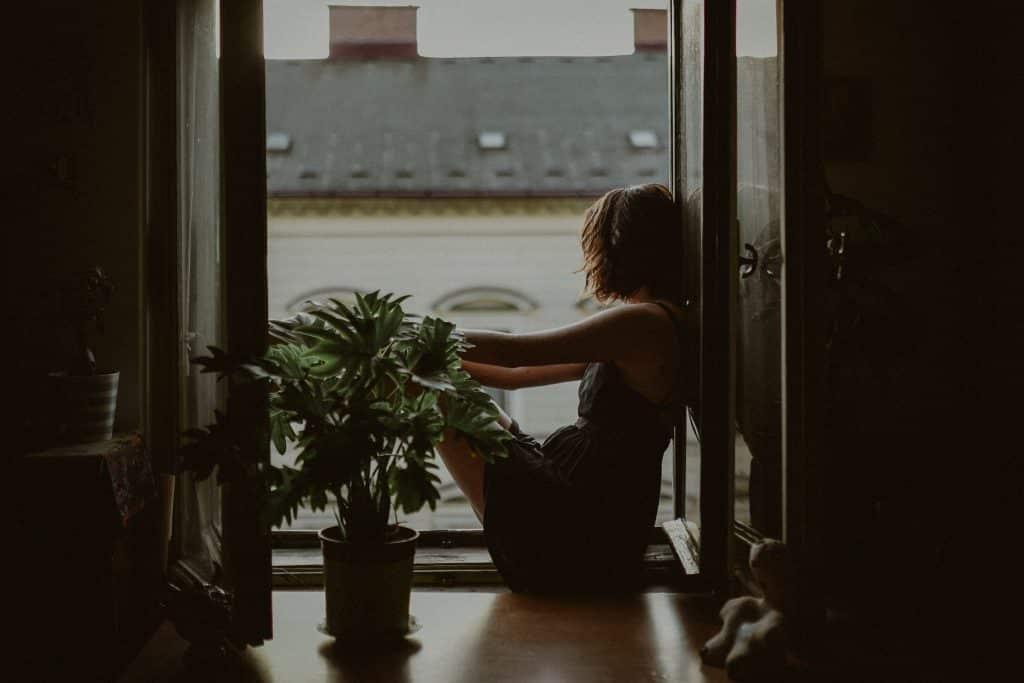 Mulher sentada na janela olhando para fora