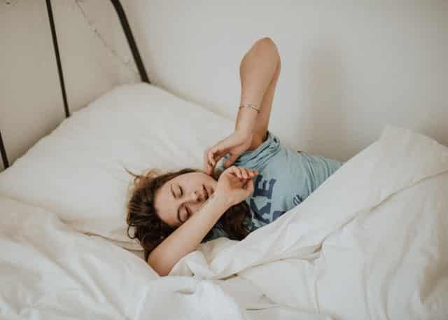 Garota deitada na cama com olhos fechados e expressão triste