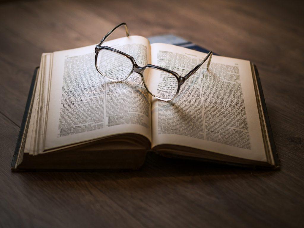 Imagem de um livro de Kepler aberto sobre uma mesa de madeira. Sobre o livro um óculos de grau.