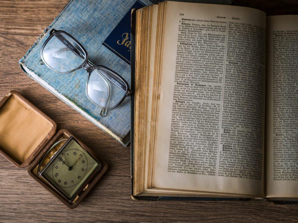 Imagem do livro de Kepler aberto sobre uma mesa. Ao lado dele um óculo de grau, uma agenda de capa azul e um relógio antigo.