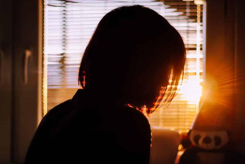 Silhueta de uma mulher olhando para a janela com o pôr do sol
