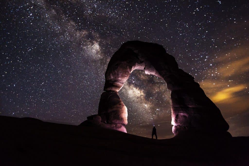 Homem em uma estrutura de rochas à noite. Ao fundo há um céu muito estrelado.
