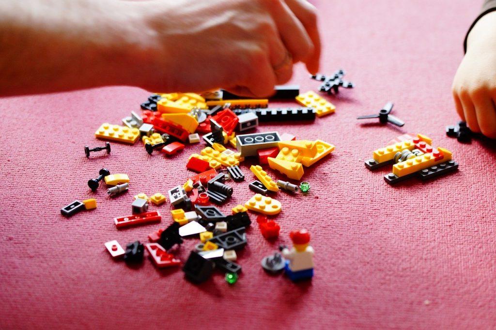 Mãos de duas pessoas brincando com peças de Lego.