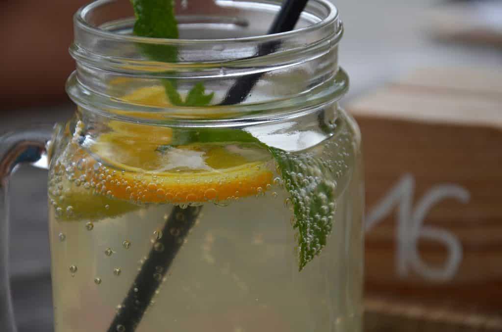 Imagem de uma jarra de vidro cheia de limonada com água de coco e hortelã.