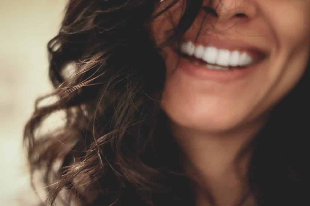 Mulher sorrindo com seu cabelo no rosto