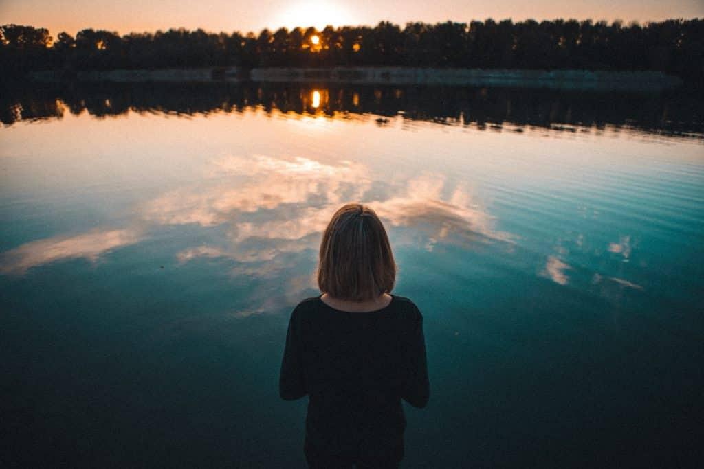 Mulher olhando para o mar a sua frente