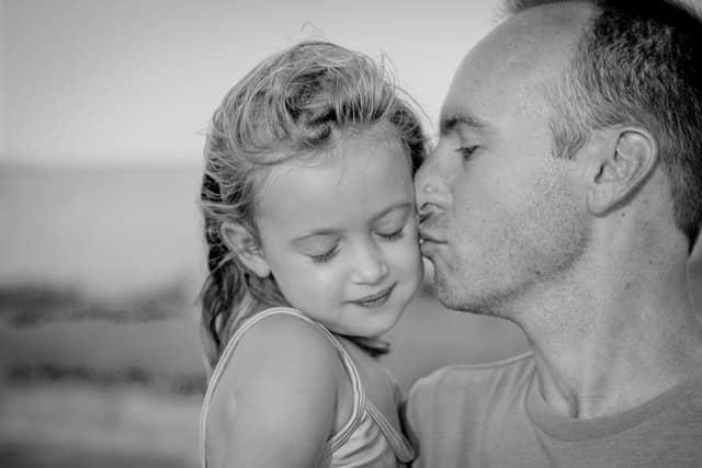 Pai dando beijo no rosto de filha pequena em foto preta e branca