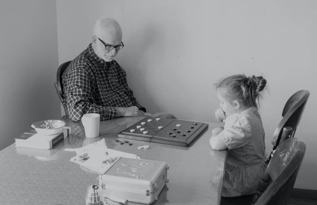 Menina sentada à mesa jogando damas com seu avô.