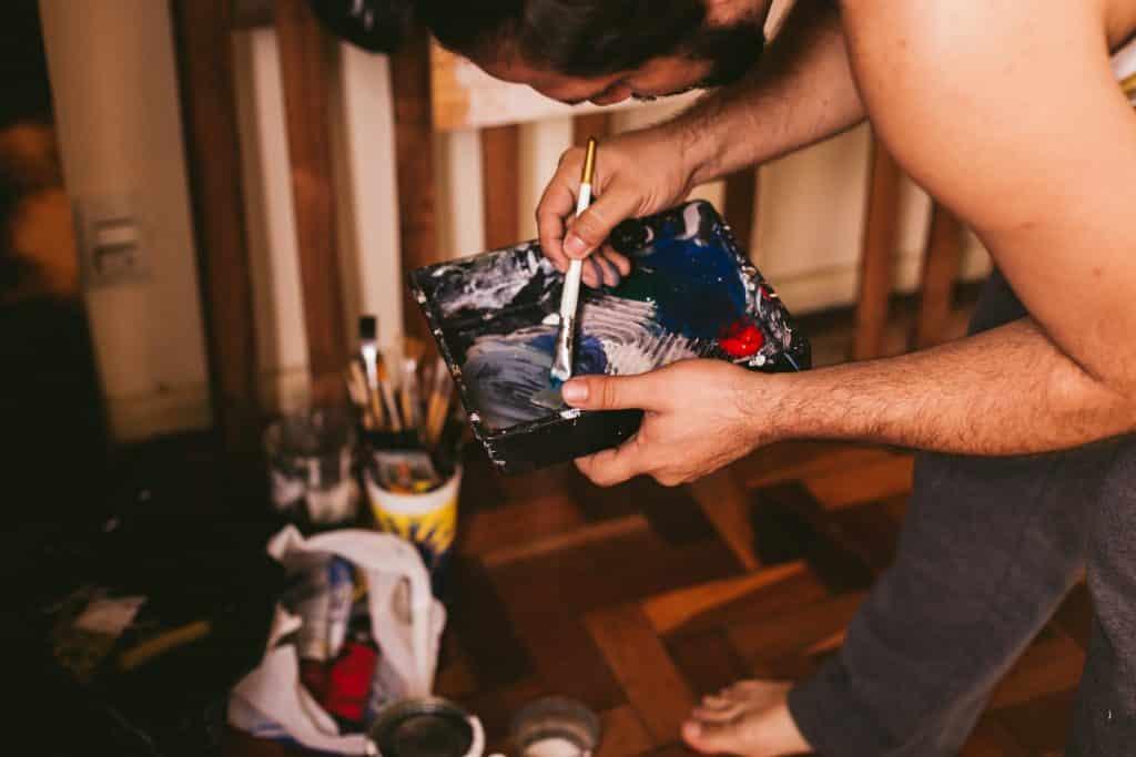 Homem segurando um pote retangular com tinta dentro.