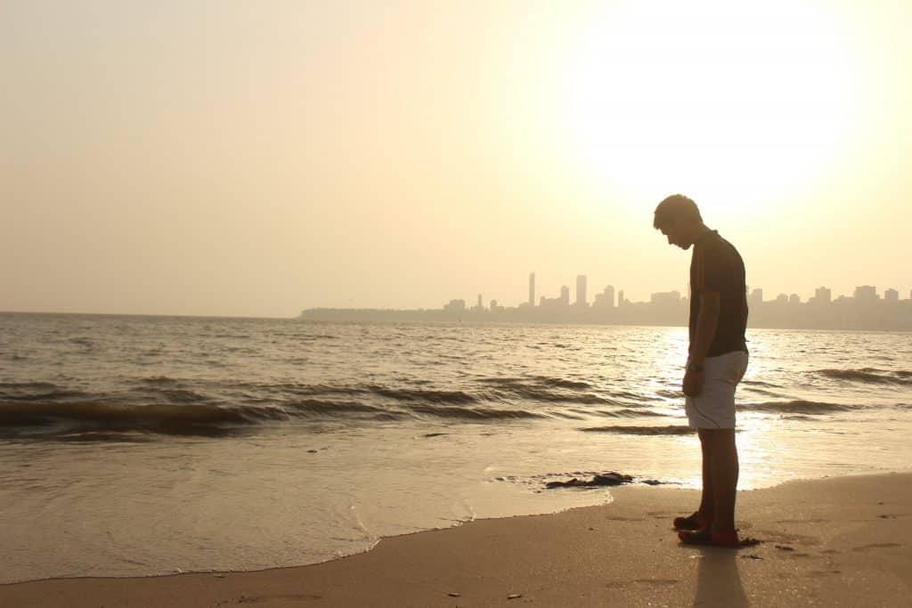 Homem em pé na praia, em frente ao mar, com a cabeça baixa.