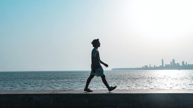 Homem caminhando em parapeito com mar ao fundo
