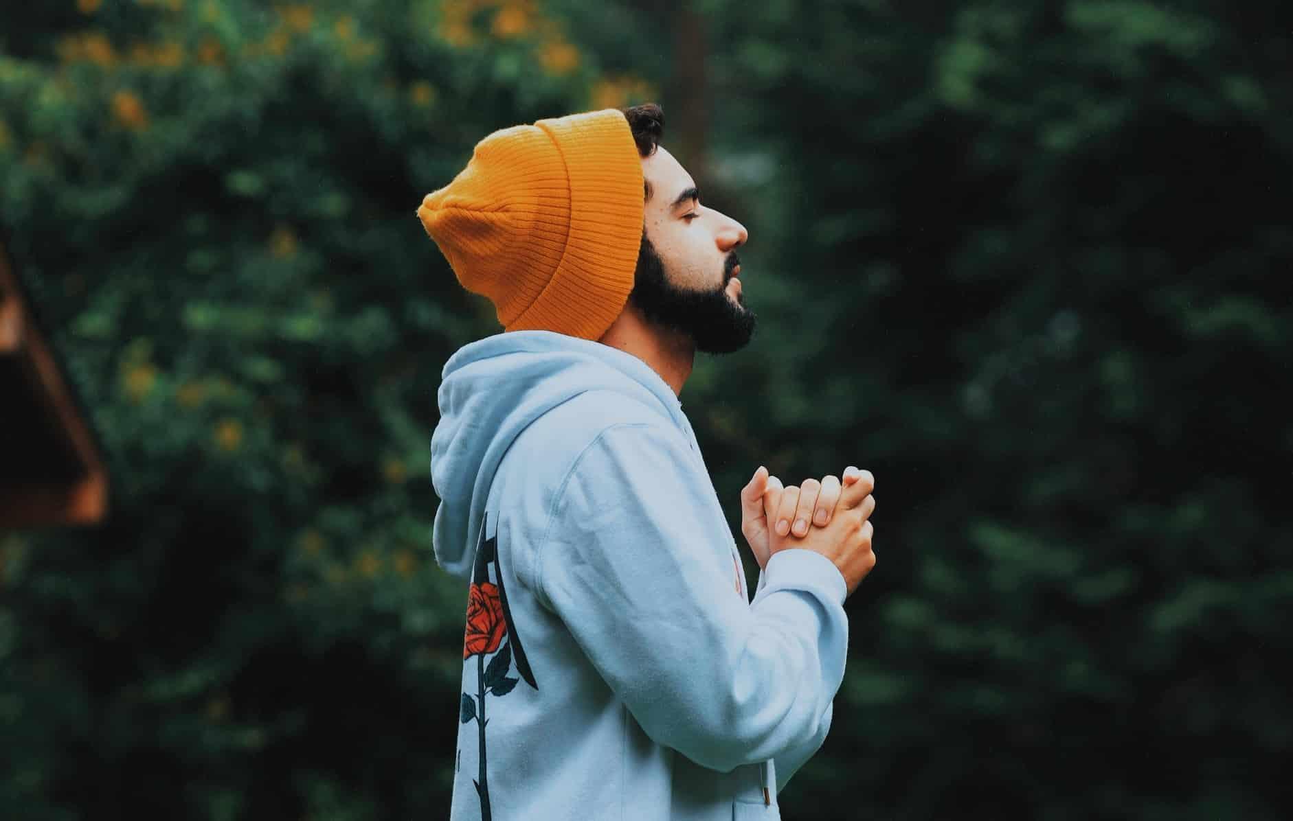 Homem de perfil rezando