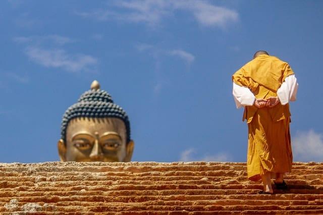 Monge subindo escadaria visto de costas com rosto de estátua de buda ao fundo