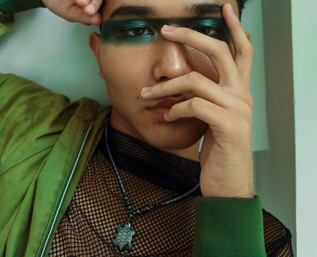 Homem usando uma tinta verde brilhante em volta dos olhos