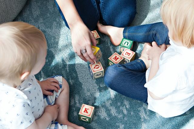 Mãe com filhas pequenas brincando no sofá