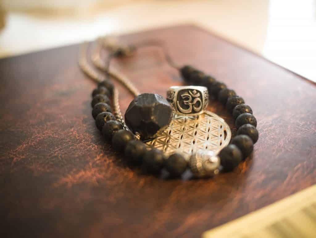 Pulseira e anel marrons com símbolo OM.