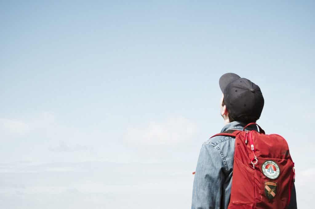 Homem olhando para o céu, usando boné e com mochila nas costas