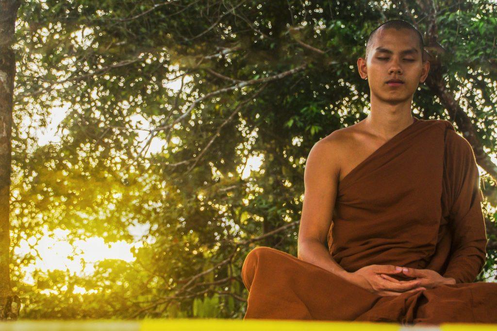 Imagem de um monge sentado em um gramado fazendo meditação.