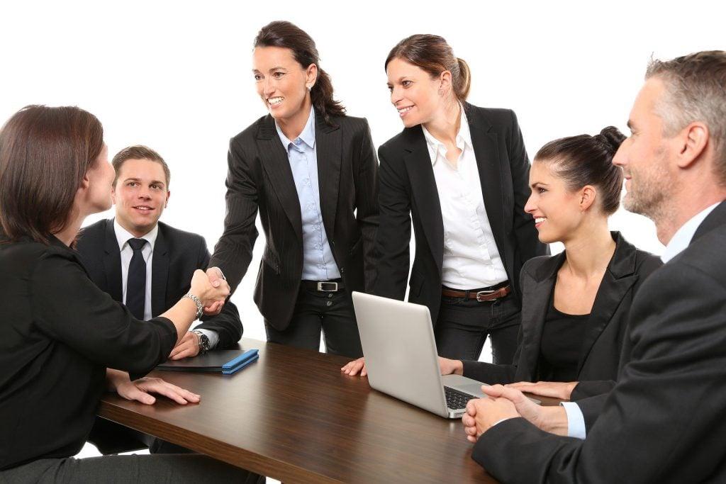 Imagem de mulheres e homens e uma mesa de negociação em um ambiente corporativos. Ambos, mulheres e homens vestem ternos e camisas, representando a igualdade de gênero.