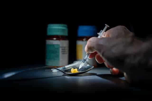 Mão segurando seringa apoiada em substância química em colher de metal