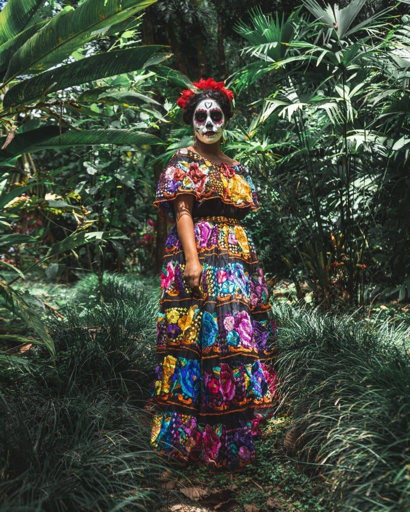 Mulher com vestido colorido, coroa de flores vermelhas e maquiagem à caráter do Día de Los Muertos