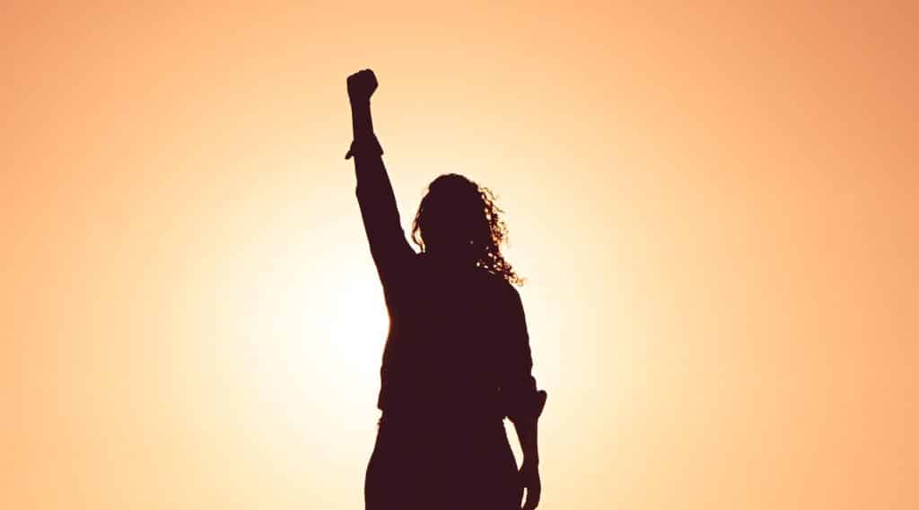Filhueta de mulher com braço para cima e sol refletindo