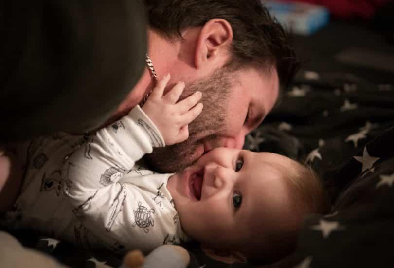 Pai beijando bochecha do bebê sorrindo deitado na cama