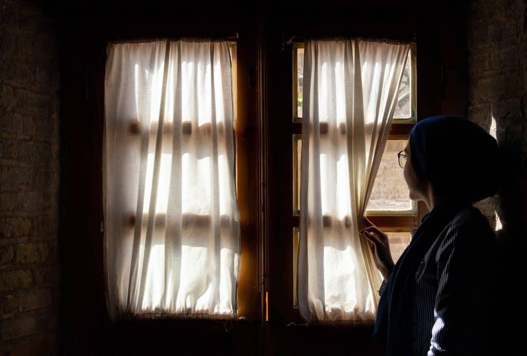 Mulher olhando para fora da jenala afastando com sua mão a cortina