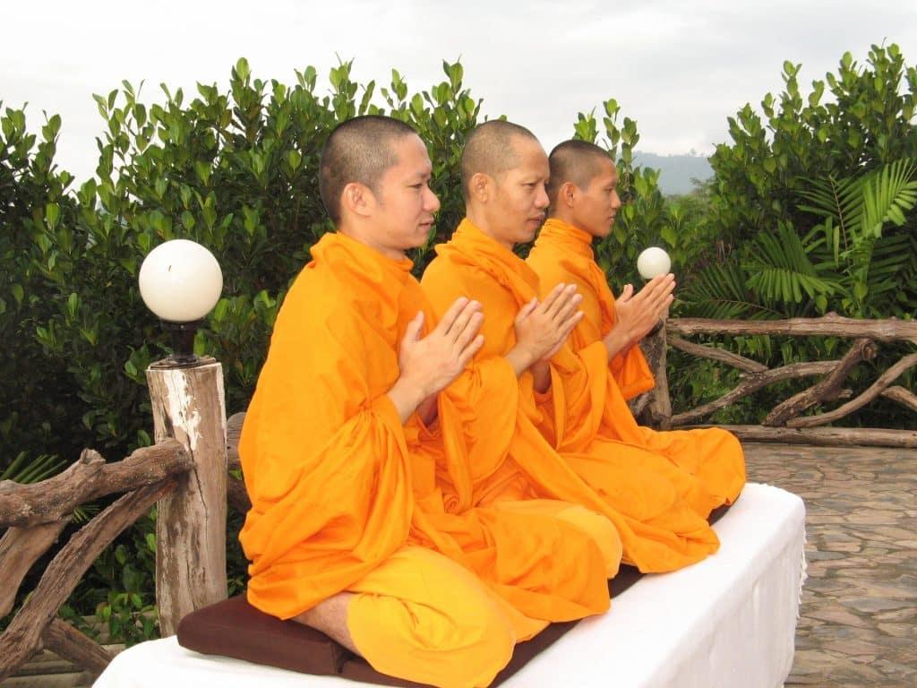 Imagem de três monges praticando a meditação.