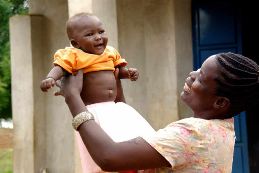 Imagem de uma mãe africana segurando em seus braços seu lindo garoto recém nascido.