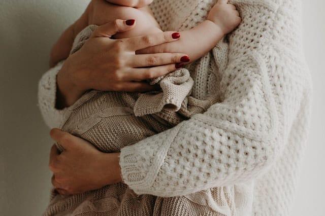 Corpo de mãe segurando o filho nos braços sem mostrar os rostos