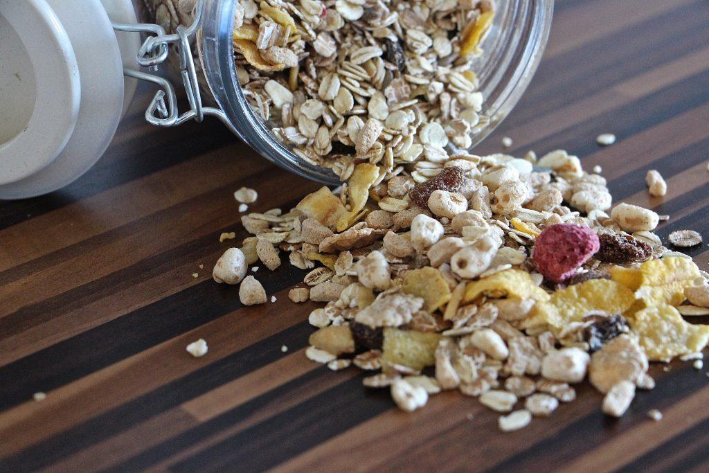 Imagem de vários tipos de cereais espalhados sobre uma mesa de madeira. Eles estão sendo selecionados para a produção da barra de cereais caseira.