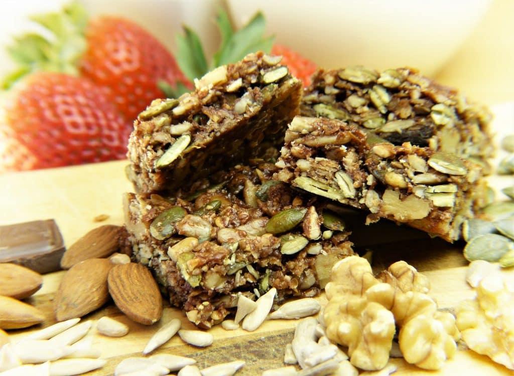 Imagem de uma barra de cereais feita com vários tipos de grãos e frutas com mel.