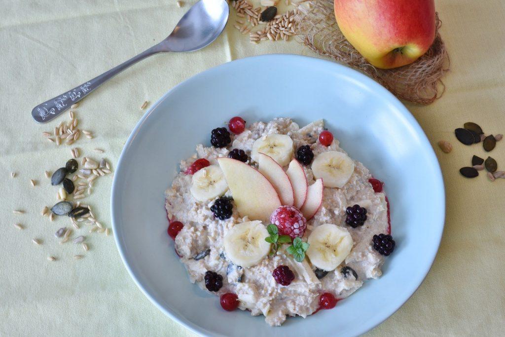 Imagem de um prato fundo de porcelana branca com cereais e frutas como banana, maça e framboesa.