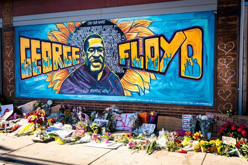 Homenagem para George Floyd com um grafite em um muro e cartazes, flores no chão