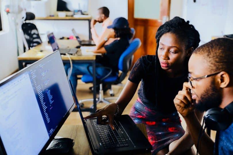 Mulher mostrando algo no computador para homem ao seu lado