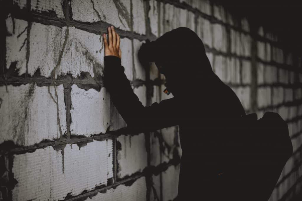 Homem usando jaqueta de moletom com touca, apoiando seus braços na parede