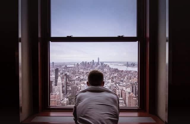 Homem de costas em janela com vista para cidade
