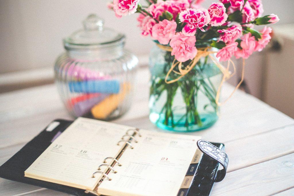 Imagem de uma agenda sobre uma mesa para preparar o planejamento para o ano novo. Ao lado um vaso de flores rosas e um pote com giz colorido.